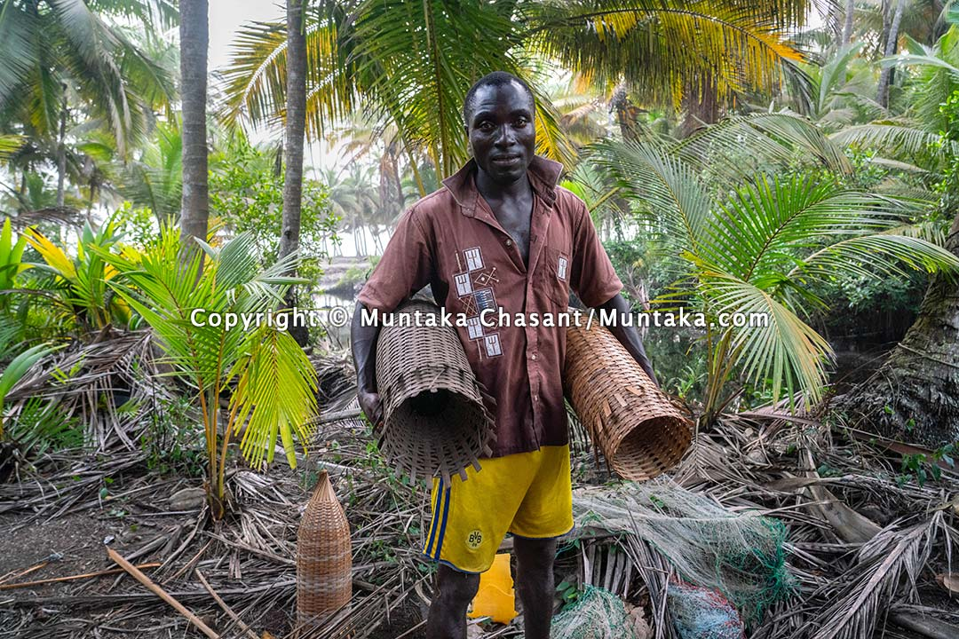 Tropical fisherman holds handmade traps. Copyright © 2021 Muntaka Chasant