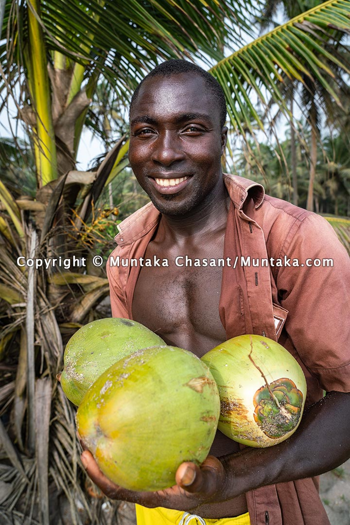 Man smiles after plucking coconuts on the coast of Ghana. Copyright © 2021 Muntaka Chasant