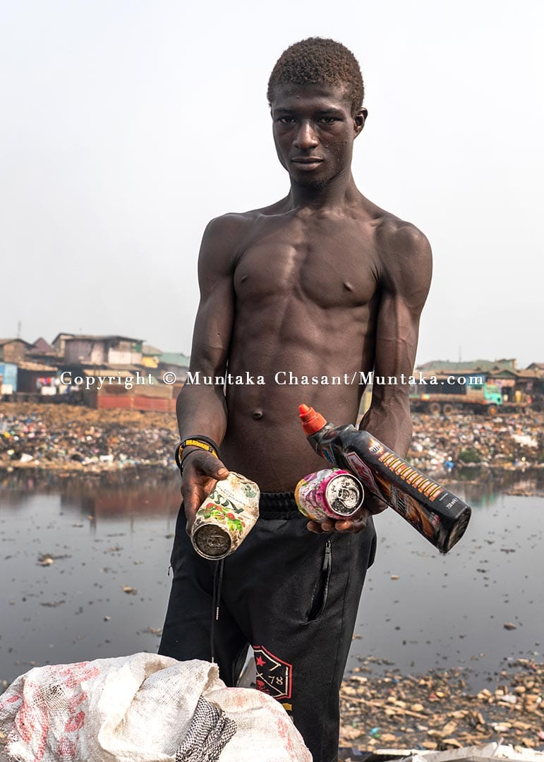 Urban poor man displays cans and plastic materials he had recovered from the polluted Korle Lagoon. Copyright © 2021 Muntaka Chasant