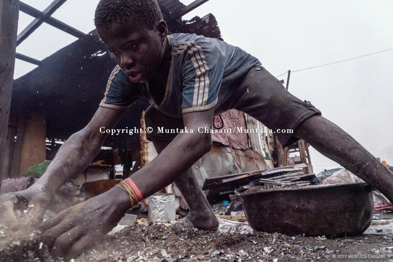 In The Rain: A 16 years old boy scrabbles at the ground during a rainfall event for pieces of AC condenser fins. © 2019 Muntaka Chasant