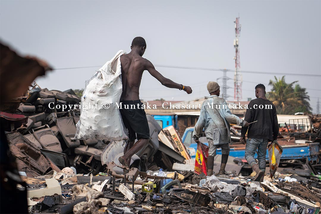 An urban poor man walks barefooted on an e-waste dumpsite strewn with broken CRT TV glass. Agbogbloshie, Ghana. Copyright © 2021 Muntaka Chasant