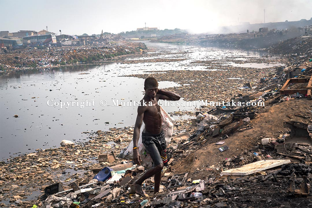 Youth poverty in Ghana: A 28 years old urban poor man trudges up from the heavily polluted Korle Lagoon after recovering recyclable materials. Copyright © 2021 Muntaka Chasant