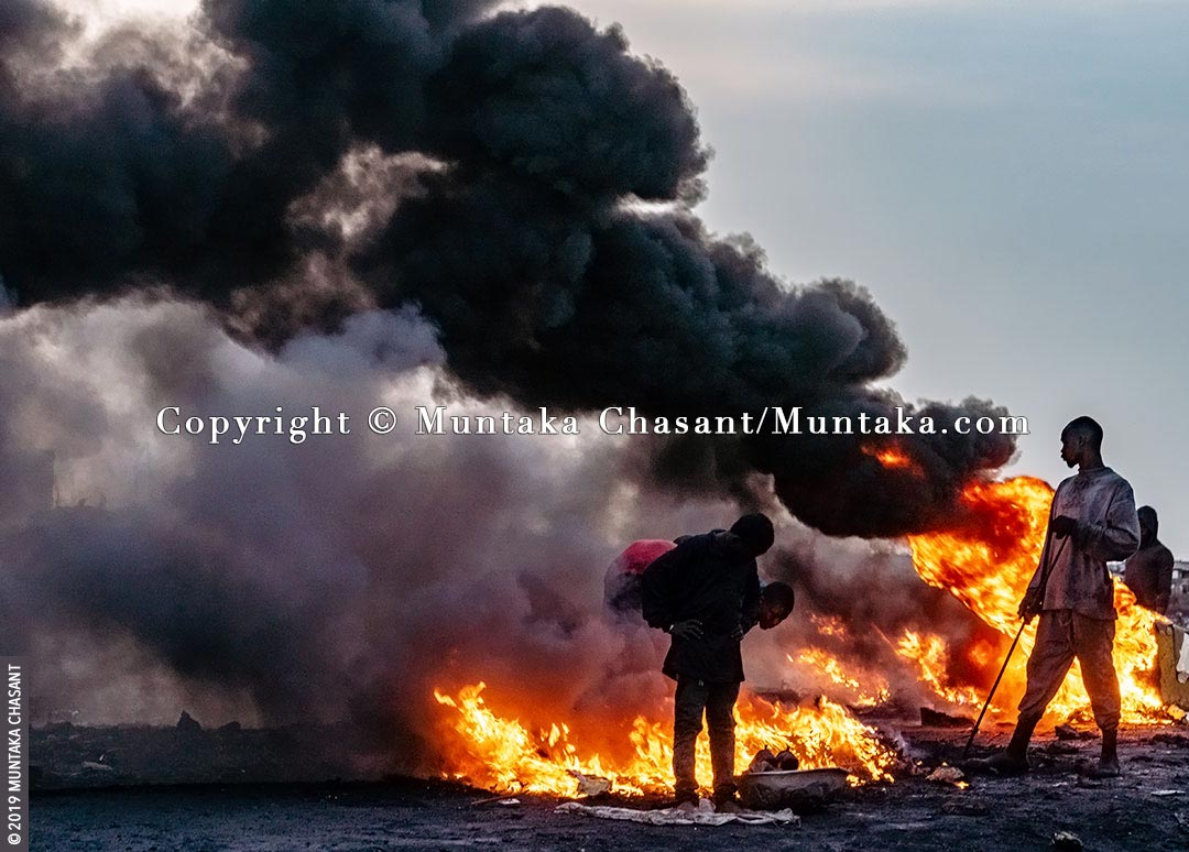 Agbogbloshie, Ghana: Men are burning cables in the open to recover the copper materials inside. It had rained heavily, and the man in the black shirt is keeping himself warm as he waits for his copper wires. © 2019 Muntaka Chasant
