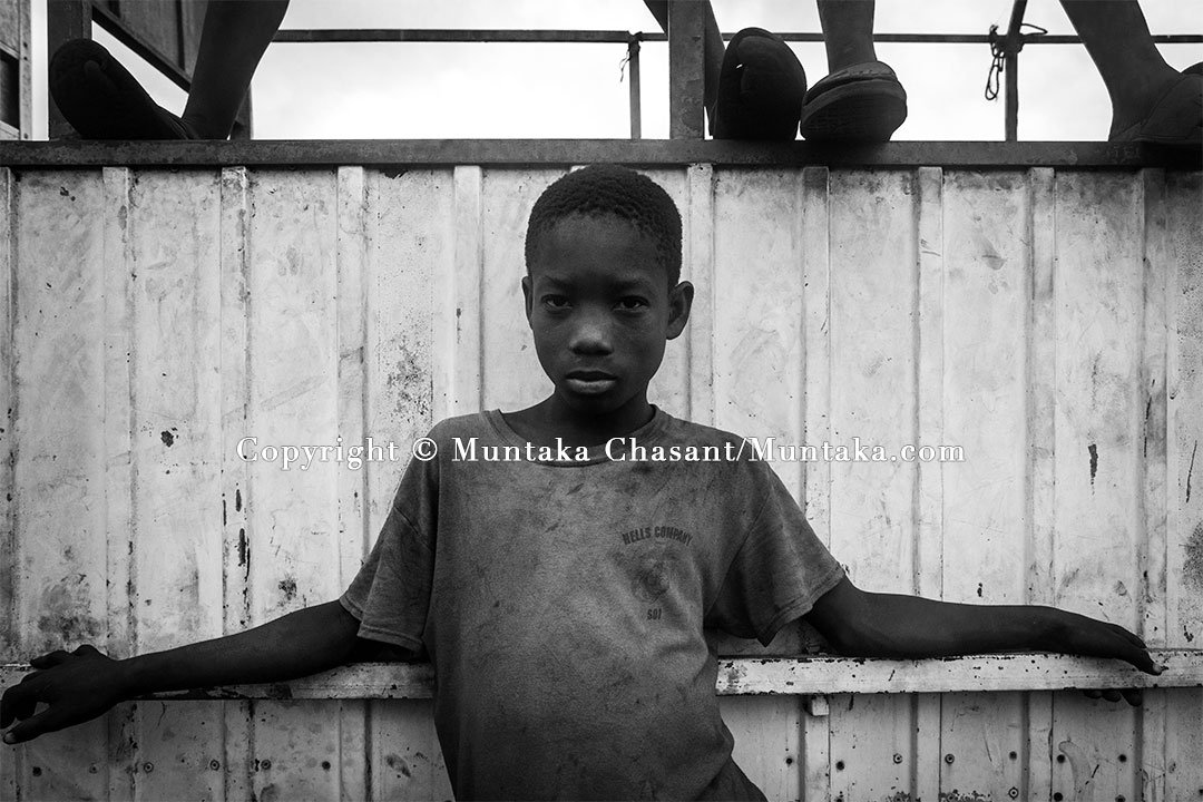 Child Labour: 13-year-old hazardous child labourer leans against a scrapped truck — by the Korle Lagoon. Copyright © Muntaka Chasant