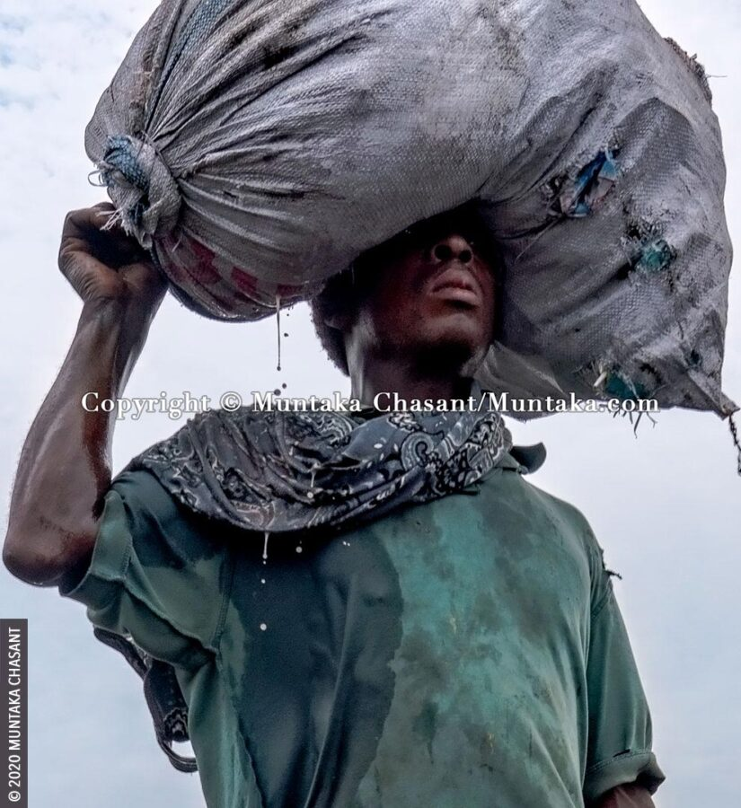 Human suffering: Poor man carries a plastic sack on his head with liquid dripping from it. More than 700 million people worldwide live on less than $2 a day. © 2020 Muntaka Chasant