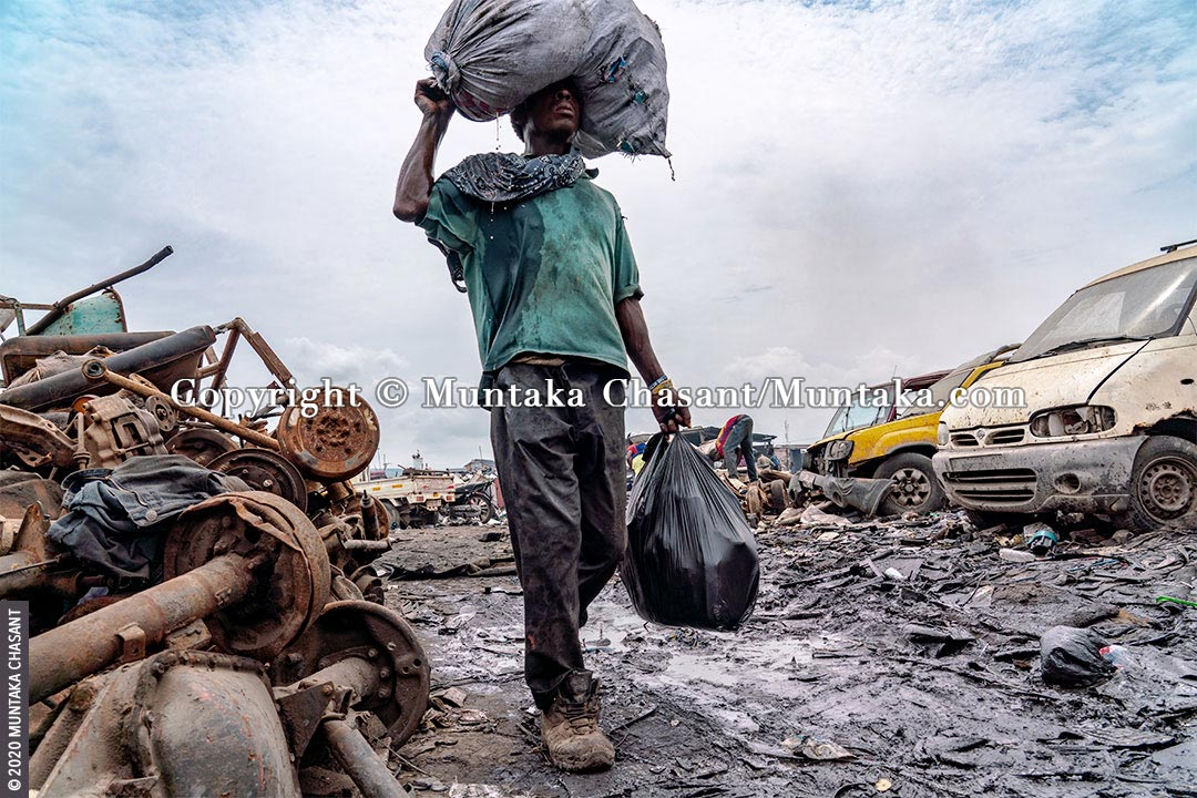 Urban Suffering: Urban poor man carries a plastic sack on his head with liquid dripping from it in Accra, Ghana. 41% of people in Africa live in extreme poverty, with the World Bank estimating that nearly 9 out of every 10 people in extreme poverty will be living on the continent by 2030. © 2020 Muntaka Chasant