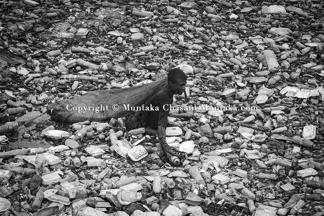 Youth poverty: A frustrated young Ghanaian man swims in the heavily polluted Kore Lagoon to recover recyclable plastics and cans. Copyright © Muntaka Chasant