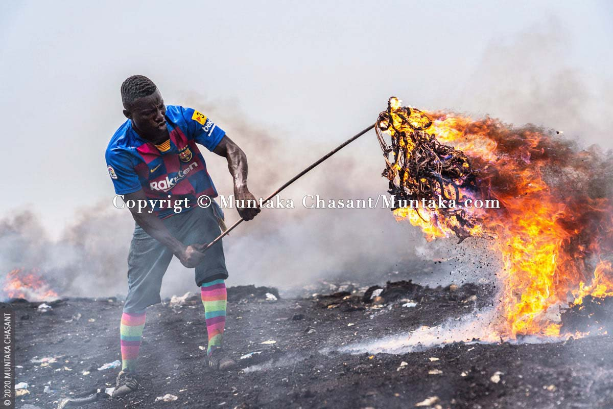 Agbogbloshie: Man is burning electrical wires to recover the copper materials inside at Agbogbloshie, Ghana. © 2020 Muntaka Chasant