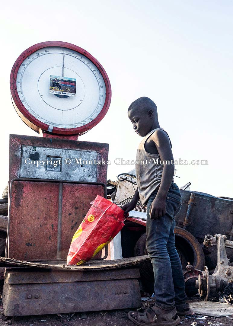 Child Labour in Ghana: Eight years old Akufo-Addo, engaged in hazardous child labour, is weighing scrap metals at Agbogbloshie, Ghana. More than 24% of children aged 15-14 in Ghana are engaged in the worst forms of child labour, a 2018 US Department of Labor report has found. © 2020 Muntaka Chasant
