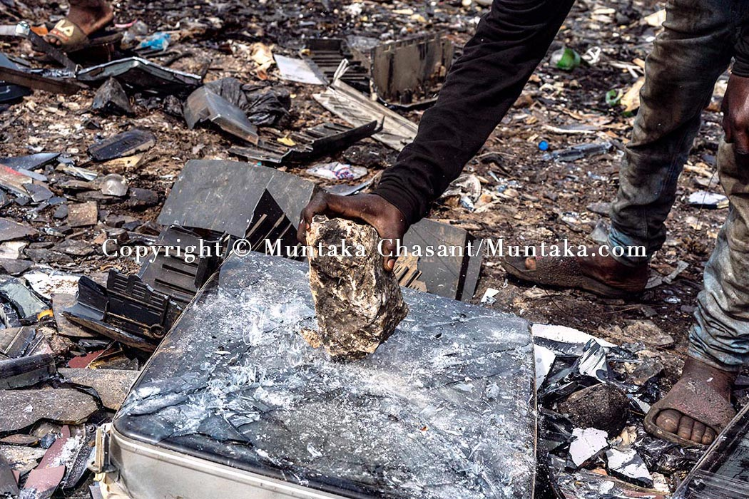 Primitive e-waste recycling: Young man uses a rock to break apart an old CRT TV to reclaim the iron materials inside, Agbogbloshie, Accra, Ghana. © 2020 Muntaka Chasant