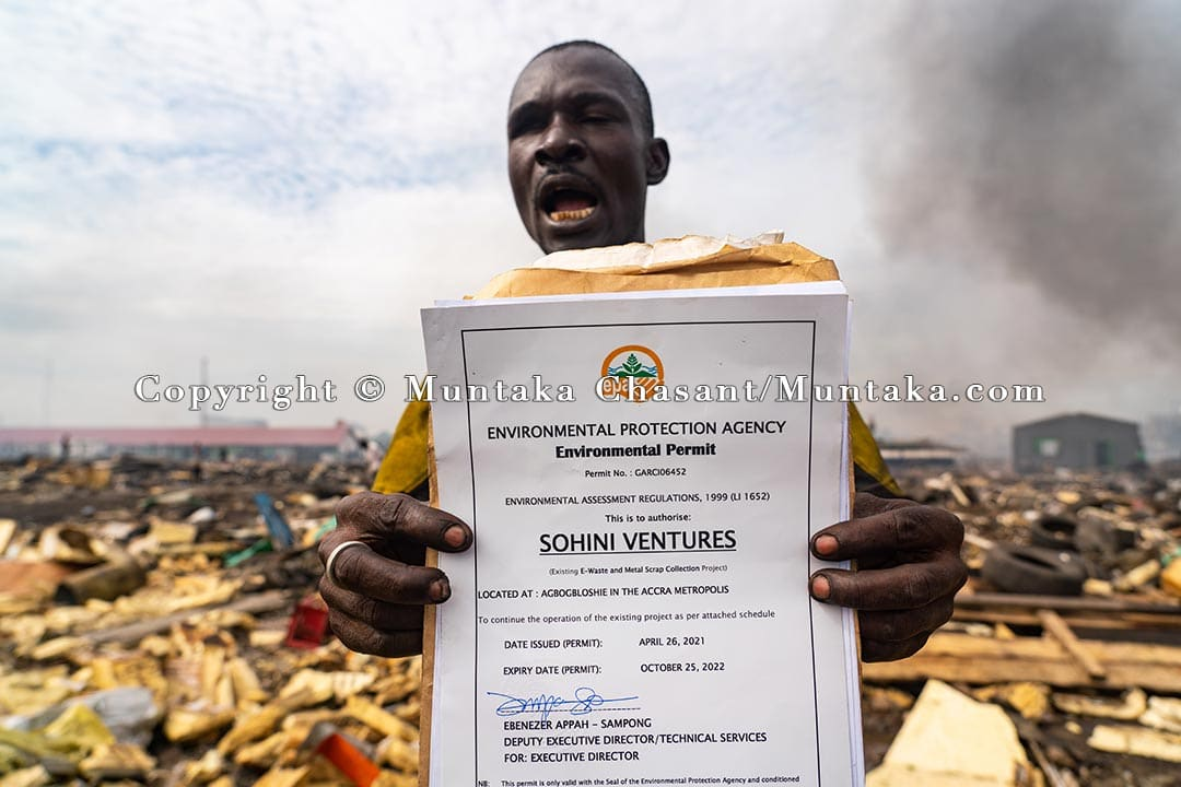 """Exasperated Amadu displays his April 2021 authority-issued environmental permit and other papers granted to him by Ghana's Environmental Protection Agency to operate his scrap business at Agbogbloshie. """"They took my money and have now destroyed my business, why?"""" Infuriated Amadu yelled. Copyright © Muntaka Chasant"""