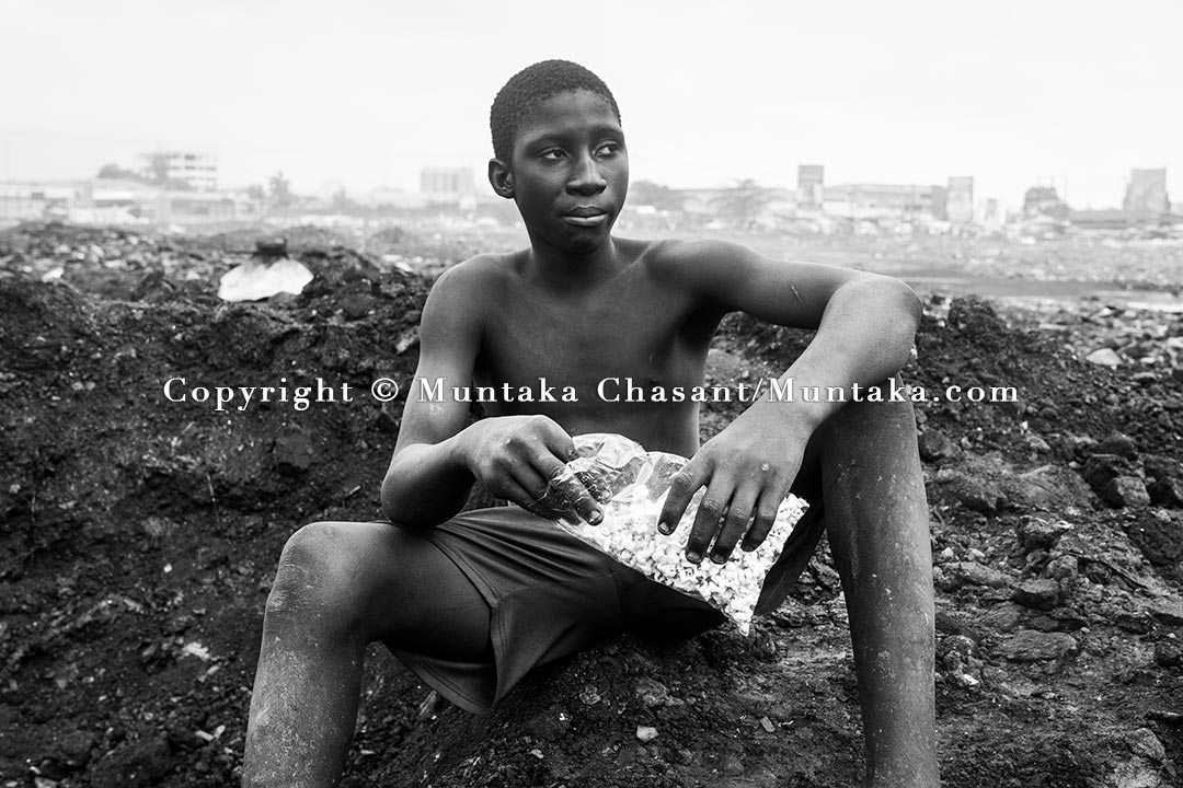A teenager engaged in hazardous child labour takes a break to eat popcorn at Agbogbloshie, Accra, Ghana. Copyright © Muntaka Chasant