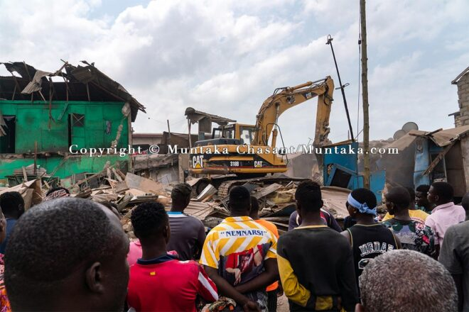 Old Fadama residents anxiously watch on as an excavator demolish sections of the settlement. Copyright © Muntaka Chasant