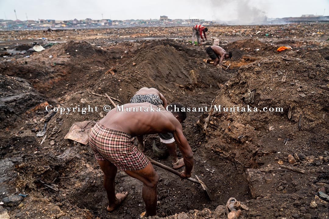 Desperate urban poor men dig deep into the surface to unearth scrap metal 10 weeks after the Agbogbloshe demolition. Copyright © Muntaka Chasant