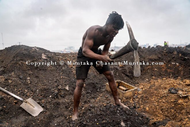 Desperate urban poor man digs deep into the surface of the demolished Agbogbloshie site to find scrap metal. Copyright © Muntaka Chasant